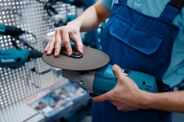 Mannelijke werknemer in uniform kiezen scherpe schijf voor haakse slijper in gereedschapsopslag. keuze uit professionele apparatuur in ijzerhandel, instrumentensupermarkt