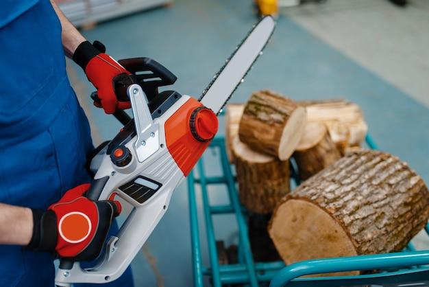 Mannelijke werknemer in uniform testen kettingzaag in gereedschapsopslag. keuze uit professionele apparatuur in ijzerhandel, elektrisch instrument