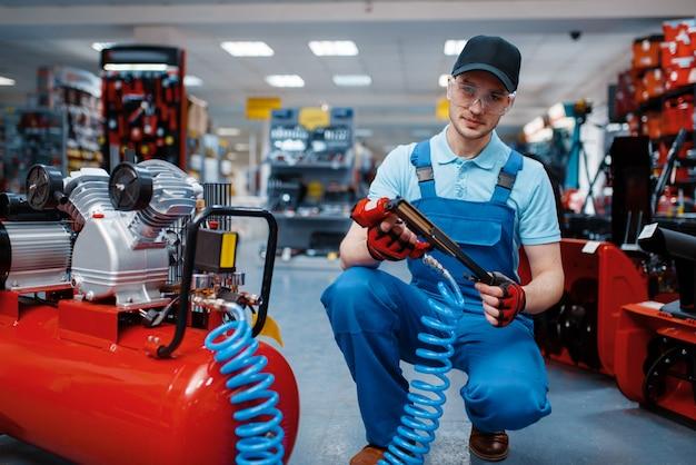 Mannelijke werknemer in uniforme poses met pneumatische spijkermaker in gereedschapsopslag. keuze uit professionele apparatuur in ijzerhandel, instrumentensupermarkt