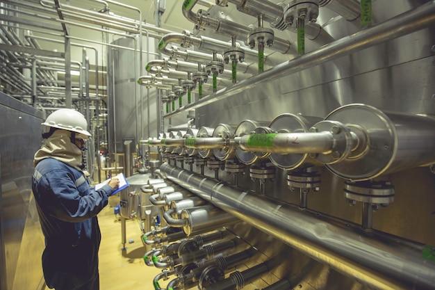 Mannelijke werknemer inspecteert het proces van voedseldrank bij de productiepijpleiding en roestvrijstalen tank