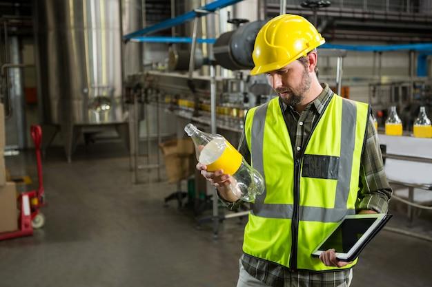 Mannelijke werknemer inspecteren flessen in sap-fabriek