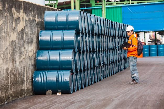 Mannelijke werknemer inspectie record drum olie voorraad vaten blauw horizontaal of chemisch voor in de industrie.