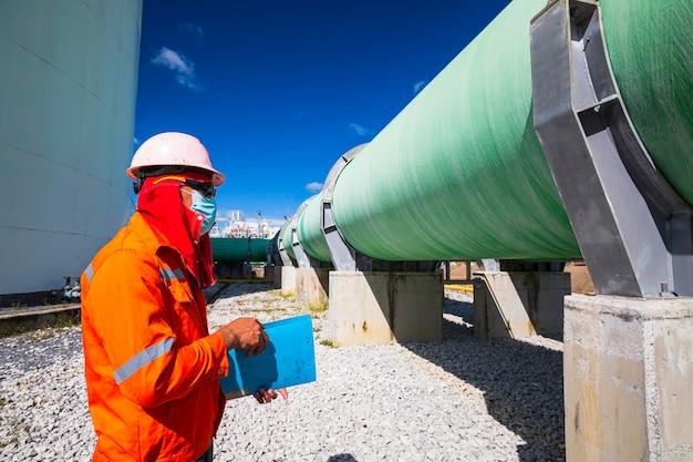 Mannelijke werknemer inspectie visuele grote pijpleiding groene elektriciteitscentrale genereert elektriciteit, water en gas.