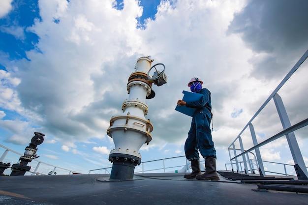 Mannelijke werknemer inspectie visuele klep pijpleiding en bovenste dak opslagtank ruwe olie