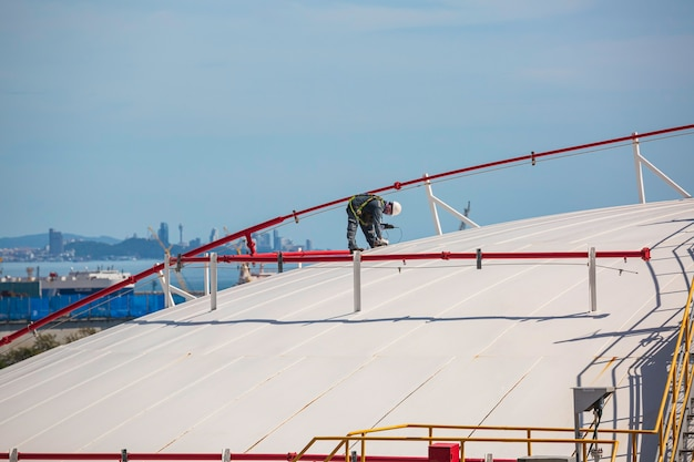 Mannelijke werknemer is voor inspectie van ultrasone dikte dakplaat koepel top van opslagtank.