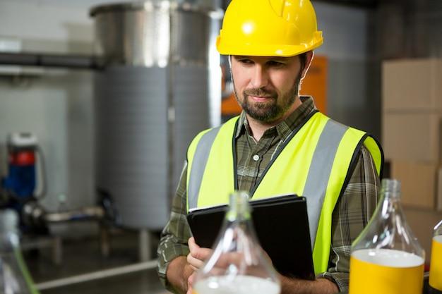 Mannelijke werknemer met behulp van digitale tablet in fabriek