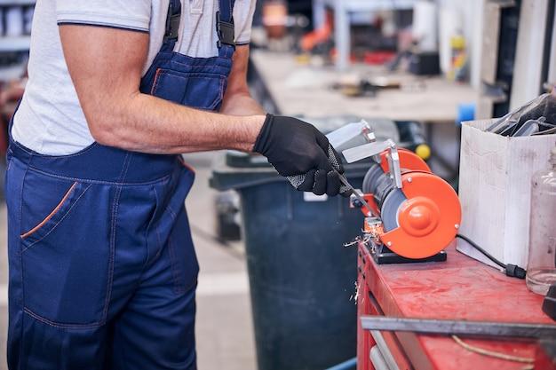 Mannelijke werknemer met behulp van slijpmachine in garage