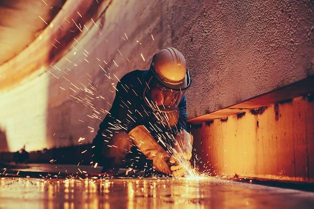 Mannelijke werknemer metaal snijdende vonk op tankbodem stalen plaat met flits van snijlicht