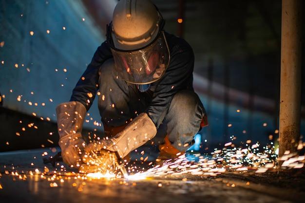 Mannelijke werknemer metaalsnijdende vonk op tankbodem stalen plaat met flits van snijlicht close-up, draag beschermende handschoenen en masker in de zijruimte.