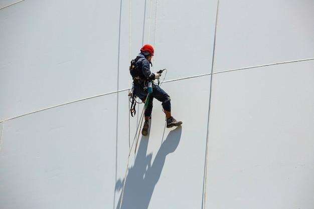 Mannelijke werknemer naar beneden hoogte tank schaal plaat touw ladder toegang veiligheidsinspectie van dikte opslagtank gas propaan.