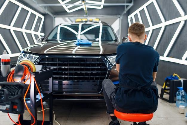 Mannelijke werknemer polijst auto oppervlak met behulp van polijstmachine, detaillering.
