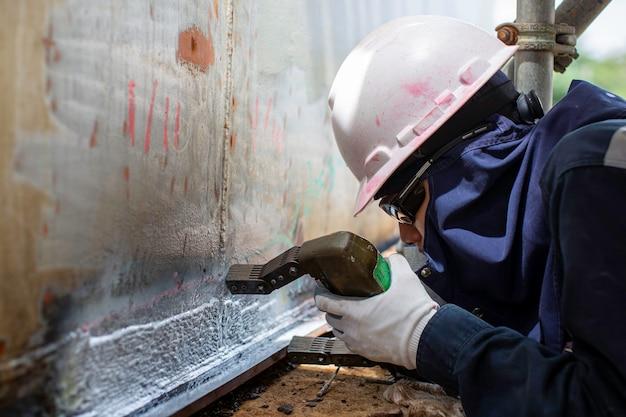 Mannelijke werknemer test stalen tank stomplas overlay carbon schaal plaat van opslagtank olie wit contrast van magnetisch veld test