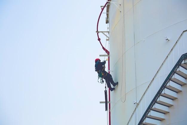 Mannelijke werknemer touw toegang hoogte veiligheidsinspectie van dikte opslag olie- en gastankindustrie