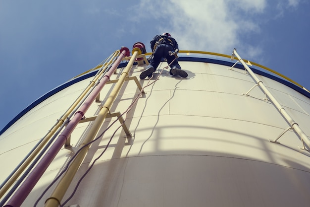 Mannelijke werknemer touwtoegang inspectie van dikte shell plaat opslagtank olie-industrie.