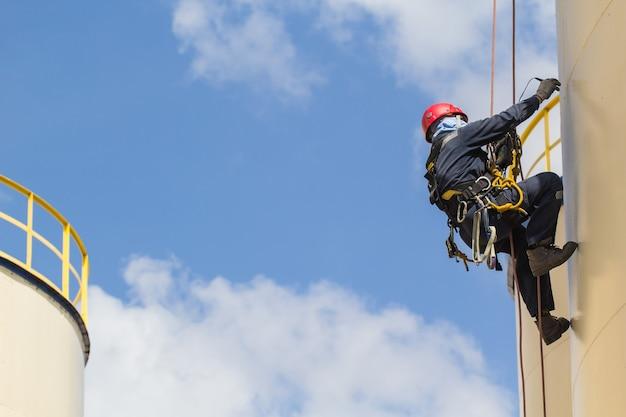 Mannelijke werknemer touwtoegangsinspectie van de industrie van de dikteopslagtank.