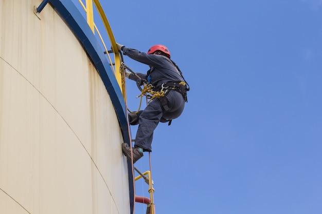 Mannelijke werknemer touwtoegangsinspectie van de olie-industrie voor opslagtanks.