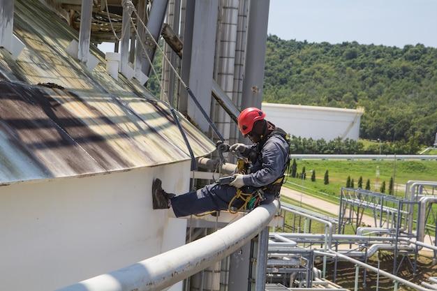 Mannelijke werknemer touwtoegangsinspectie van dikte dakopslagtank en brandwater