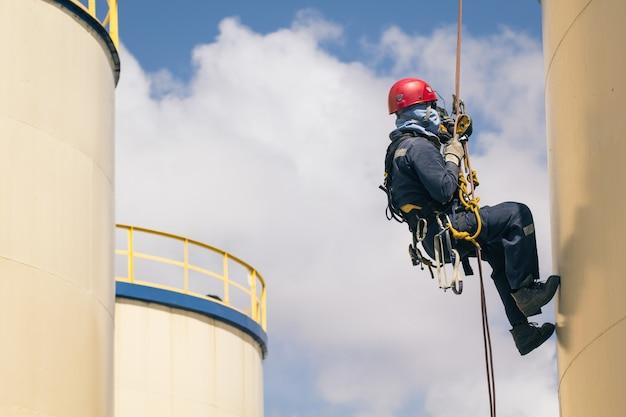 Mannelijke werknemer touwtoegangsinspectie van dikte shell plaat opslagtank olie-industrie en blauwe lucht.