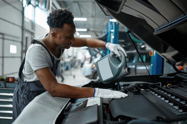 Mannelijke werknemer verandert olie in motor, autoservice. auto reparatie garage, man in uniform, auto station interieur