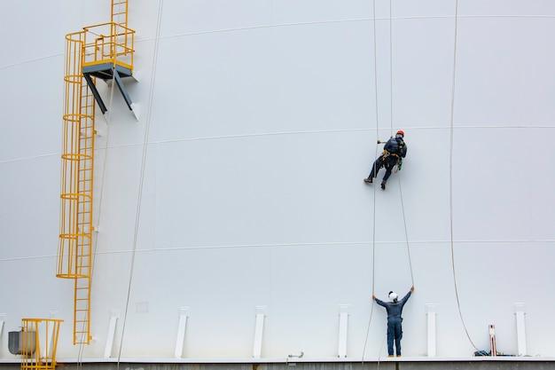 Mannelijke werknemers controleren de kabel naar beneden, de toegang tot de tank, de inspectie van de dikte van de schaal van de schaal van de opslagtank, veiligheidswerkzaamheden op hoogte.