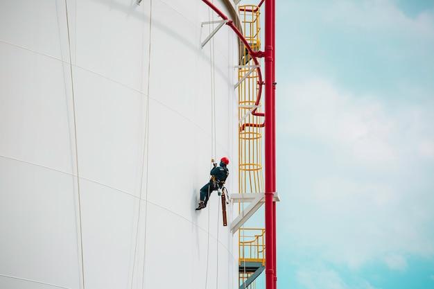 Mannelijke werknemers controleren de kabeltoegangsinspectie van de tank met touw naar de dikte van de schaalplaatopslagtankgasveiligheidswerk op hoogte.