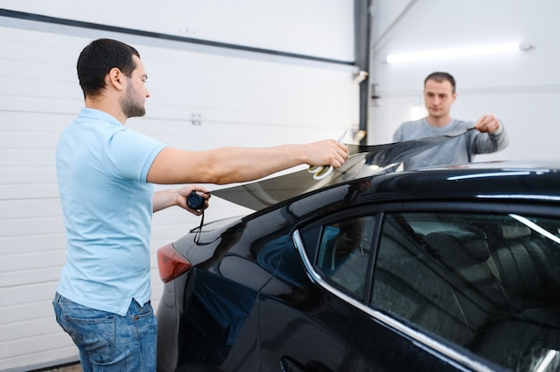 Mannelijke werknemers houden vel auto verven, tuning service. monteurs die vinyltint toepassen op autoruit in garage, getint autoglas