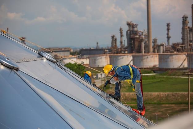 Mannelijke werknemers touwtoegangshoogtebeveiliging verbinden met een knoopveiligheidsharnas, vastklikken in dakvalstop en valbeveiligingsankerpuntsystemen klaar om op te stijgen, bouwplaatsolietankkoepel