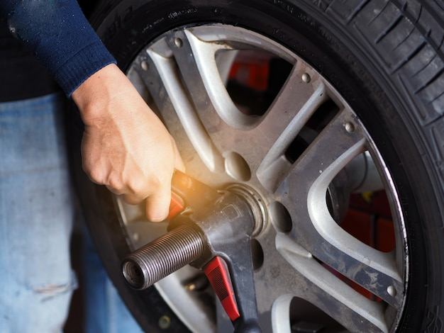 Mannelijke werktuigkundige die auto'swiel in werkplaatspost herstellen