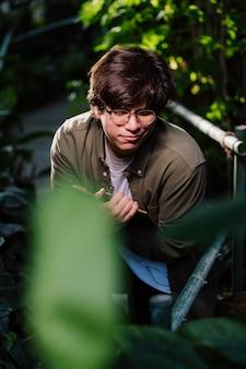 Mannelijke wetenschapper verstopt in het struikgewas. natuurbescherming concept.