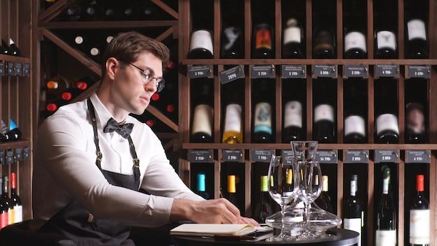 Mannelijke wijnsteward inventariseert wijn in de winkel, schrijft enkele aantekeningen in een notitieboek naast rekken met wijnflessen
