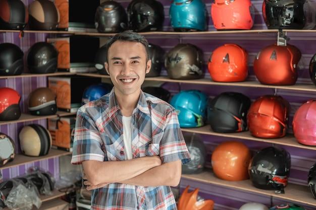 Mannelijke winkelbediende lachend met gekruiste handen in helmen winkel