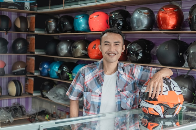 Mannelijke winkelbediende permanent met zijn hand rustend op een helm in een helmwinkel