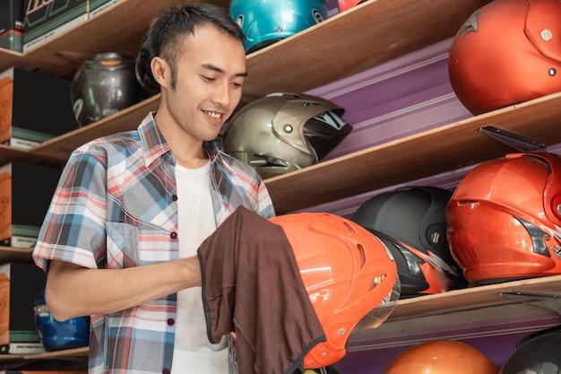 Mannelijke winkelbediende staat het schoonmaken van een helm met een doek in een helmwinkel