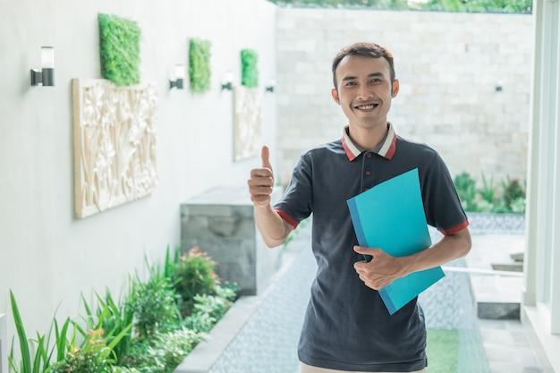 Mannelijke woningontwikkelaar staat met een duim omhoog terwijl hij het certificaat van het huis op de homepage draagt