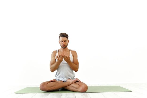 Mannelijke yoga maditaten in klassieke pose in studio op wit