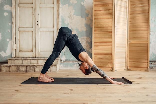 Mannelijke yoga met tatoeage aan kant doen rekoefening op mat in sportschool met grunge interieur. fit workout binnenshuis