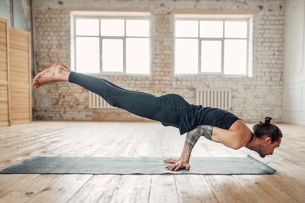 Mannelijke yoga staande op handen ondersteboven