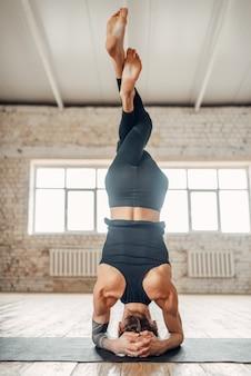 Mannelijke yoga staat op het hoofd in de sportschool, evenwichtsoefening op mat. fitnesstraining binnenshuis. gezonde levensstijl, meditatie