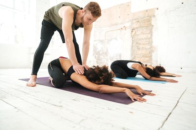 Mannelijke yogainstructeur die vrouw helpen zich uit te rekken