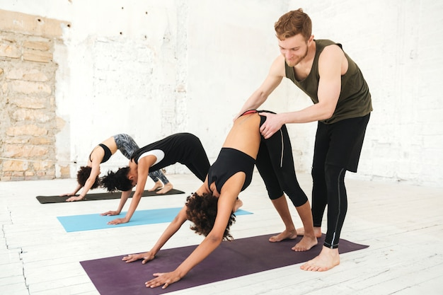 Mannelijke yogatrainer die een vrouw helpt om yogarekken te doen