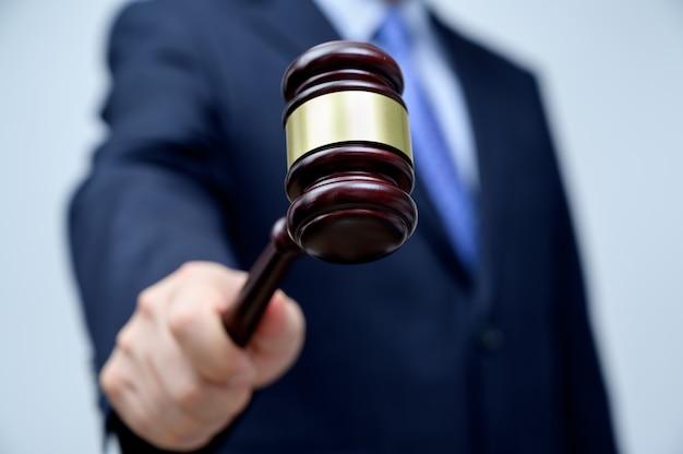Mannelijke zakenman die een hamer in hand houdt. justitie en veiling concept.