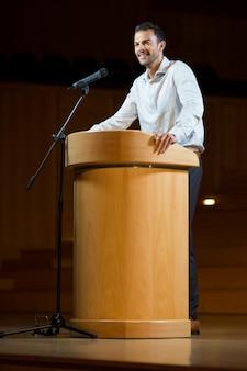 Mannelijke zakenman die een toespraak houdt op conferentiecentrum