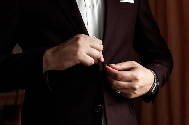 Mannelijke zakenman die zijn jasje dichtknoopt