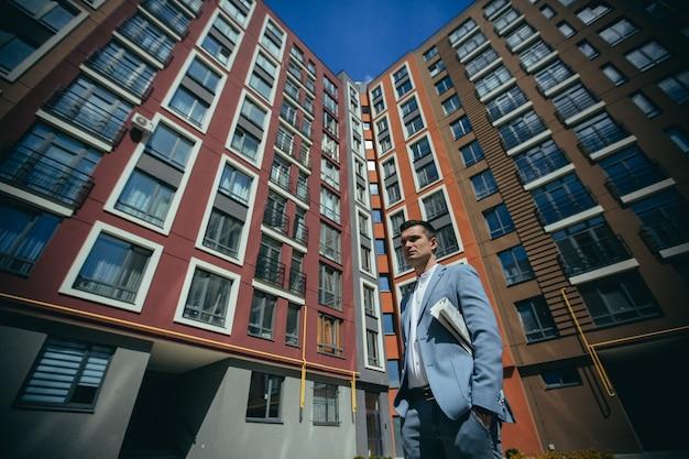 Mannelijke zakenman in een pak naast een groot zakencentrum en een modern gebouw