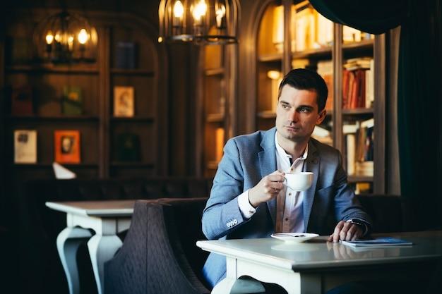 Mannelijke zakenman in een pak rusten en werken in een café