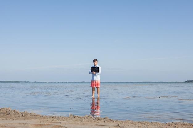 Mannelijke zakenman met elegant shirt en zwembroek met een laptop in de zee