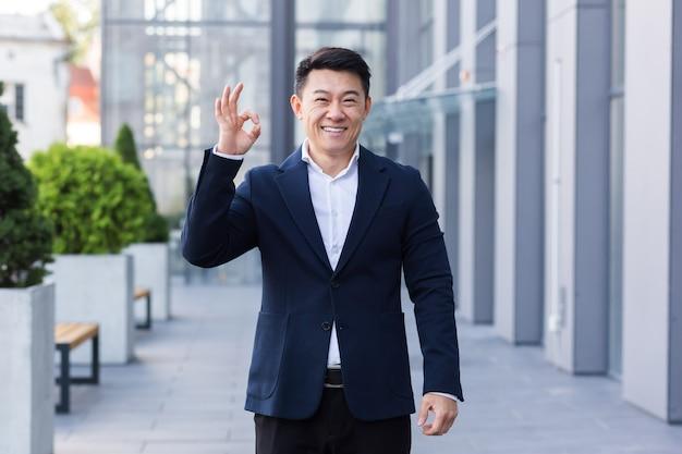 Mannelijke zakenmanverkoper aziatisch in pak glimlacht en toont zijn hand allemaal ok