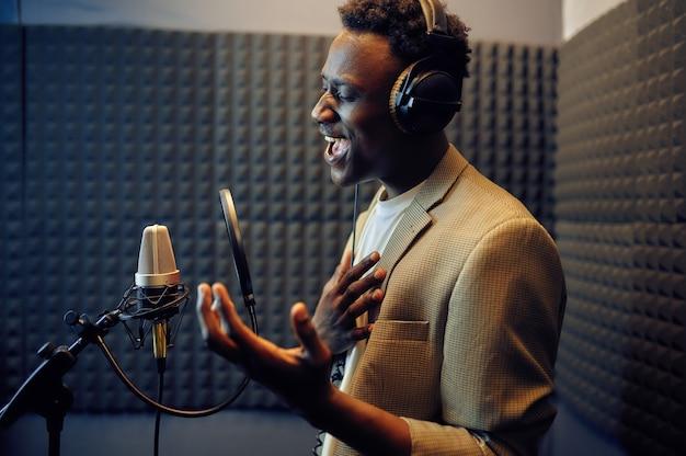 Mannelijke zanger in koptelefoon zingt een lied op microfoon, opnamestudio interieur op achtergrond. professionele spraakopname, werkplek voor muzikanten, creatief proces, moderne audiotechnologie