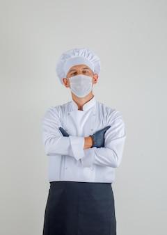 Mannelijke zich met gekruiste wapens in uniform, schort en hoed bevinden en chef-kok die zeker kijken