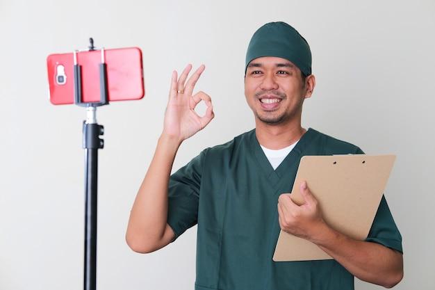 Mannelijke ziekenhuisverpleegster die een ok-teken geeft aan de patiënt tijdens online consultatie met behulp van een videogesprek via een mobiele telefoon